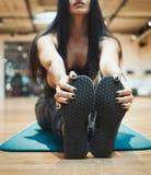 Молодая привлекательная девушка брюнет enlacing ее ботинки спорта после практиковать тренировку разминки и crossfit на голубой ци стоковая фотография