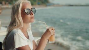 Молодая привлекательная девушка выпивая здоровый сок на пляже Сексуальный белокурый портрет с апельсином манго сток-видео
