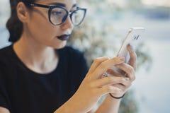 Молодая привлекательная девушка держа мобильный телефон и отправляя СМС сообщение Стоковое Фото