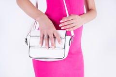 Молодая привлекательная девушка представляя с белой сумкой и розовым платьем стоковое фото rf