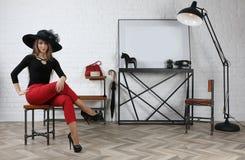 Молодая привлекательная девушка сидя на табуретке в студии стоковые изображения