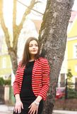 Молодая привлекательная женщина в красной куртке и черном платье на улице стоковое изображение rf