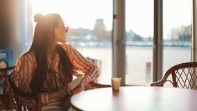 Молодая привлекательная женщина в красных солнечных очках при планшет сидя в кафе Красивая девушка в авиапорте или shoppping видеоматериал