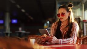 Молодая привлекательная женщина в красных солнечных очках при планшет сидя в кафе Красивая девушка в авиапорте или shoppping акции видеоматериалы