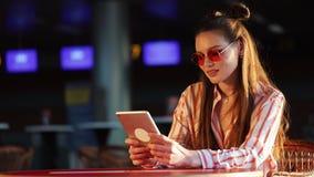Молодая привлекательная женщина в красных солнечных очках при планшет сидя в кафе Красивая девушка в авиапорте или shoppping сток-видео