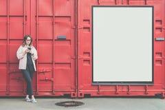 Молодая привлекательная женщина в стеклах стоит снаружи на красной предпосылке стены металла, смотря экран телефона, smartphone п Стоковая Фотография