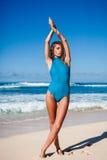 Молодая привлекательная женщина в swimwear представляя на песчаном пляже во время дневного времени Стоковые Изображения RF