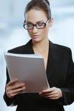 Молодая привлекательная женщина дела в стеклах читая документы подряда Стоковое фото RF
