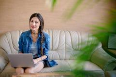 Молодая привлекательная женщина держа компьтер-книжку на ее ногах Стоковое Изображение