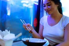 Молодая привлекательная женщина есть азиатскую еду с палочками на кафе или ресторане стоковые фотографии rf
