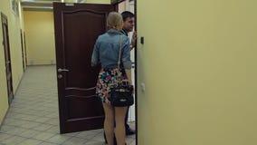 Молодая привлекательная женщина идет для того чтобы укомплектовать личным составом спор в двери в коридоре офиса сток-видео