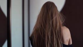 Молодая привлекательная женщина идет к ящику в живущей комнате, выбирает вверх одевает акции видеоматериалы