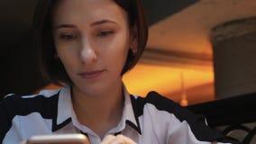 Молодая привлекательная женщина использует ее мобильный телефон в уютном ресторане кафа Она удивлена и сердита акции видеоматериалы