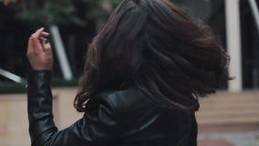 Молодая привлекательная женщина поворачивая к камере дважды с красивой улыбкой идя в улицу около современного здания сток-видео