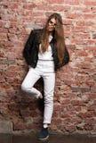 Молодая привлекательная женщина представляя против кирпичной стены Стильное appearamce, черная кожаная куртка Стоковые Фото