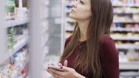 Молодая привлекательная женщина проверяя для того чтобы сделать список на смартфоне в супермаркете акции видеоматериалы