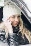 Молодая привлекательная женщина сидя в автомобиле и беседах телефоном Стоковые Изображения
