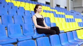 Молодая привлекательная женщина слушает к музыке на трибуне акции видеоматериалы