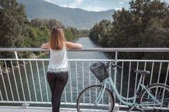 Молодая привлекательная женщина с велосипедом на мосте стоковое фото rf