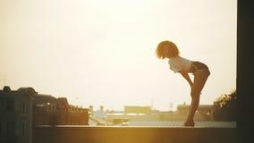 Молодая привлекательная женщина с вьющиеся волосы выполняя танцуя элементы показывая ее пластмассу - на предпосылке зданий видеоматериал