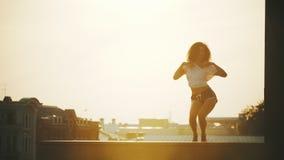 Молодая привлекательная женщина с вьющиеся волосы выполняя танцуя элементы на предпосылке зданий - заходе солнца акции видеоматериалы