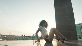 Молодая привлекательная женщина с вьющиеся волосы в высоких пятках выполняя элементы прокладки танцуя на том основании показывая  сток-видео