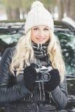 Молодая привлекательная женщина с старой камерой около черного автомобиля Стоковое Фото