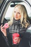 Молодая привлекательная женщина с чашкой горячих питья и донута сидит в автомобиле Стоковая Фотография