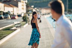 Молодая привлекательная женщина flirting с человеком на улице Flirty усмехаясь женщина смотря назад на красивом человеке Женская  стоковое фото rf