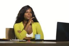 Молодая привлекательная и заботливая черная Афро-американская бизнес-леди работая на столе компьютера офиса смотря прочь думая re стоковое фото rf