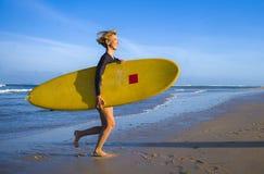 Молодая привлекательная и счастливая белокурая девушка серфера в красивом пляже нося желтую доску прибоя бежать из моря наслаждая стоковое изображение rf