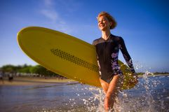 Молодая привлекательная и счастливая белокурая женщина серфера в красивом пляже нося желтую доску прибоя идя из моря наслаждаясь  стоковая фотография