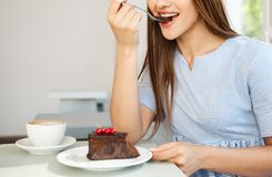 Молодая привлекательная кавказская дама наслаждается съесть шоколадный торт с горячим кофе в современной кофейне в полдень стоковое фото rf