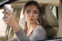 Молодая привлекательная кавказская женщина за рулем управляя автомобилем, усмехаясь и делая selfie на мобильном телефоне стоковое фото