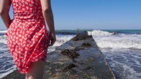 Молодая привлекательная кавказская женщина идя на пристань нося красное платье Босоногие ноги идя к морю на пристани Медленный mo сток-видео