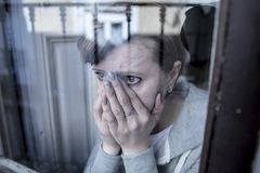 Молодая привлекательная несчастная подавленная сиротливая женщина смотря унылый смотреть через окно дома стоковые изображения