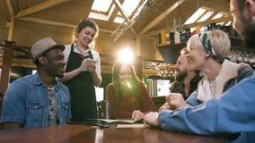 Молодая привлекательная официантка принимая заказ от группы в составе multi этнические друзья отдыхая в баре, пабе акции видеоматериалы
