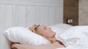 Молодая привлекательная средн-достигшая возраста белокурая женщина в белом пальто просыпает вверх в утре в кровати видеоматериал