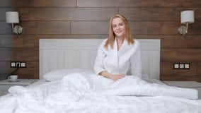 Молодая привлекательная средн-достигшая возраста белокурая женщина в белом пальто просыпает вверх в утре в кровати акции видеоматериалы