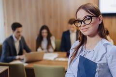 Молодая привлекательная стильная девушка работника офиса в стеклах с  стоковое фото rf