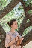 Молодая привлекательная стрельба девушки с ретро камерой под большим деревом абрикоса стоковая фотография rf