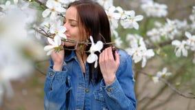 Молодая привлекательная тонкая женщина нося голубую стильную куртку джинсов представляя над цвести деревьями и цветками магнолии видеоматериал