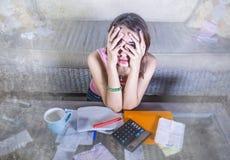 Молодая привлекательная усиленная и потревоженная испанская женщина при калькулятор и получения высчитывая ежемесячные расходы и  стоковое фото