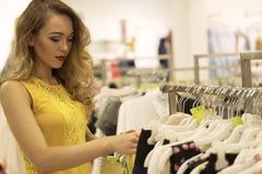 Молодая привлекательная усмехаясь девушка в желтом платье выбирает платье моды в моле Стоковые Фото