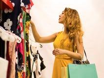 Молодая привлекательная усмехаясь девушка в желтом платье выбирает платье моды в моле Стоковые Изображения