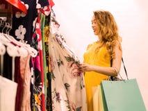 Молодая привлекательная усмехаясь девушка в желтом платье выбирает платье моды в моле Стоковое Изображение RF