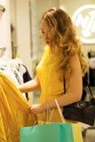 Молодая привлекательная усмехаясь девушка в желтом платье выбирает платье моды в моле Стоковая Фотография