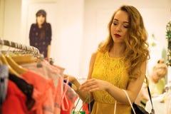 Молодая привлекательная усмехаясь девушка в желтом платье выбирает платье моды в моле Стоковое Фото