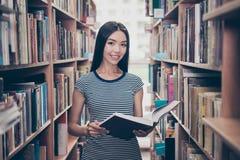 Молодая привлекательная ухищренная успешная азиатская студентка holdi стоковое изображение rf