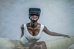 Молодая привлекательная черная афро американская женщина играя шлемофон изумлённых взглядов VR пробуя касаться иллюзии на кресле  стоковая фотография rf